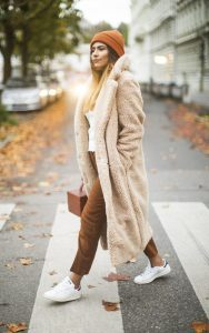 chica con abrigo camel y jersey blanco