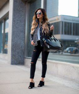 chica con vaquera negra, pantalones negros y zapatos negros