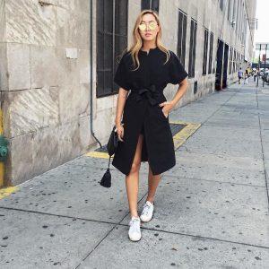 chica con vestido negro y zapatillas blancas