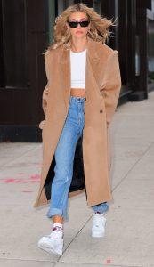 hailey con abrigo camel y sneakers blancas