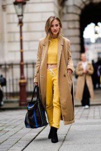 mujer con abrigo camel y chandal amarillo