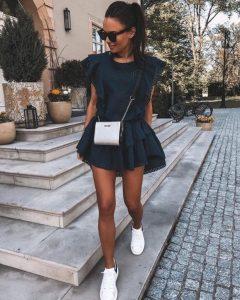 vestido negro mujer con zapatillas blancas