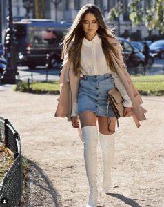 chica con falda vaquera y botas altas blancas