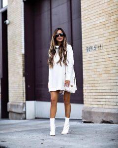 mia mine con botas blancas y jersey